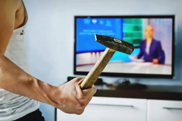 philips tv review - man about to attack his TV with a hammer