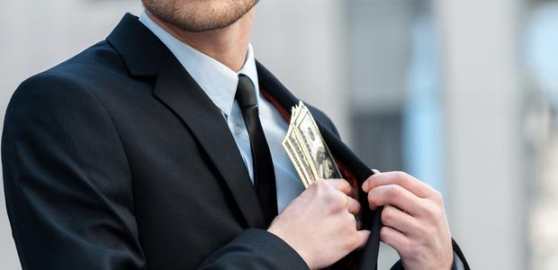 Man putting money into his coat pocket