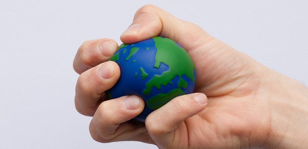 A hand squeezes a stress ball shaped like the globe