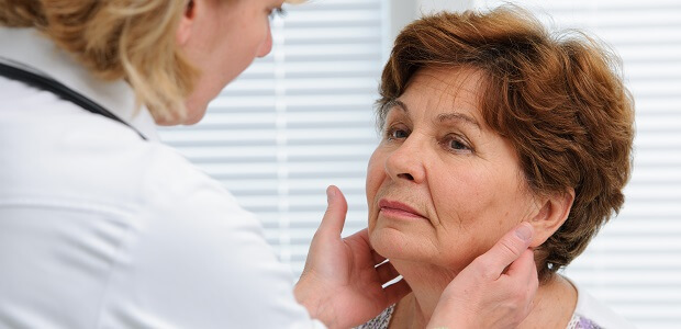 A doctor examines the thyroid of a patient with chronic fatigue