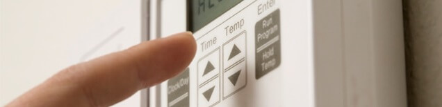 A homeowner programs a newly-installed thermostat