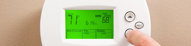 A homeowner adjusts the thermostat