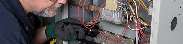 An HVAC technician works to install a furnace