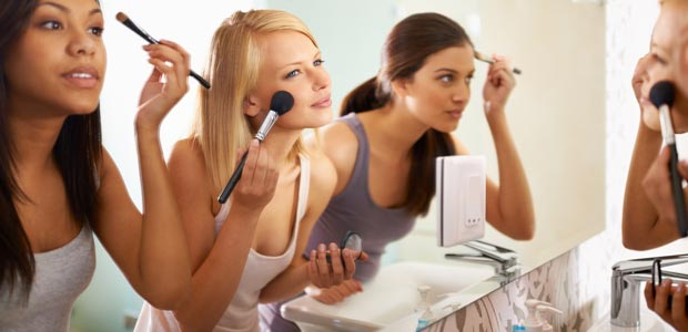 A group of women applying makeup in front of a mirror
