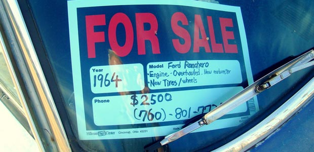 "A ""for sale"" sign on top of a car"