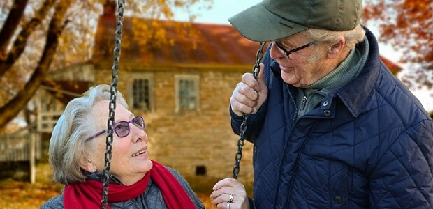 An older couple smiling at each other outdoors